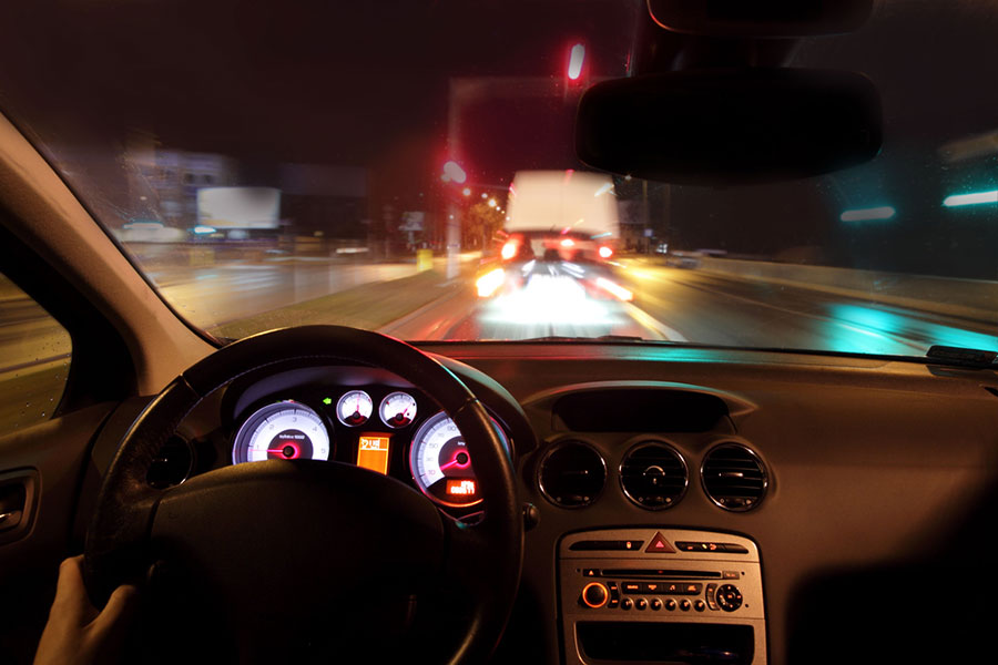 Image from the driver's perspective on a dark multi-lane highway with dashboard and blurry lights.