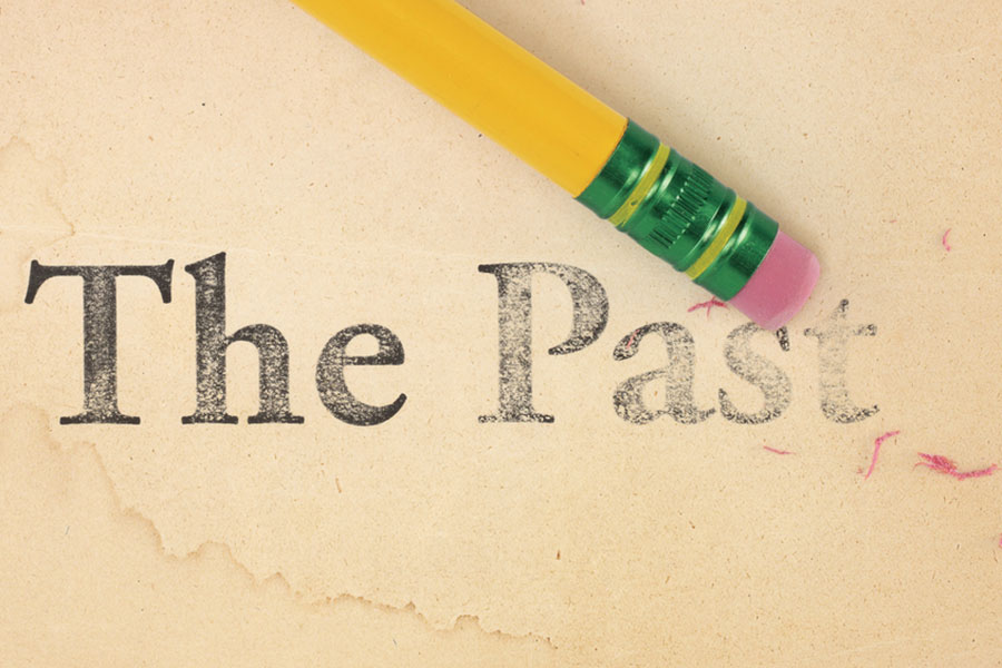 """Image of eraser end of pencil to tea stained paper removing the words """"The Past""""."""