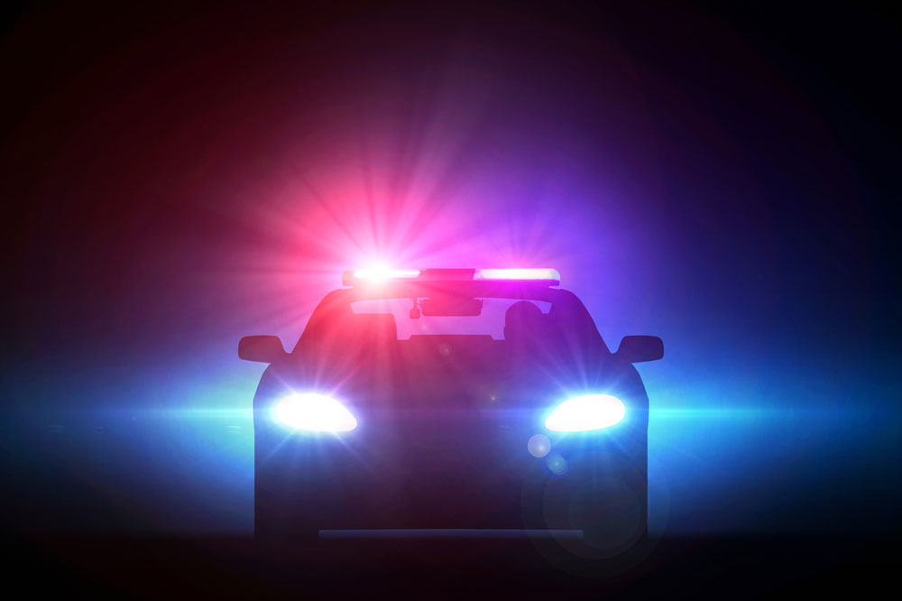 Image of police car's emergency lights cutting through the night depciting interaction with law enforcement during a traffic stop.